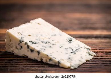 Piece of gorgonzola cheese on wooden board