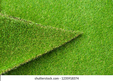Piece of Green plastic turf with selective focus. Green color Artificial grass