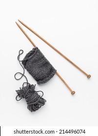 Piece of grey knitting on knitting needles