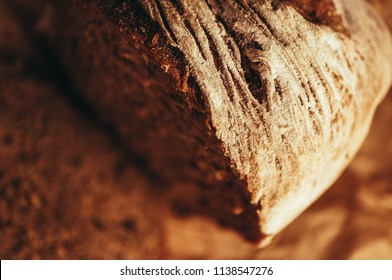 A piece of handmade freshly baked rye bread, texture background, closeup.