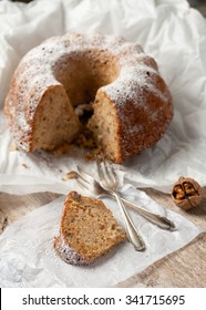 Piece of homemade apple, walnut  bundt cake with icing sugar. Selective focus.