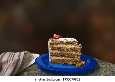 piece of homemade birthday cake on the blue plate with dark background