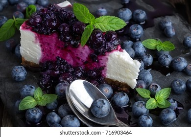 Piece of homemade cheesecake with blueberry jam and fresh ripe blueberries