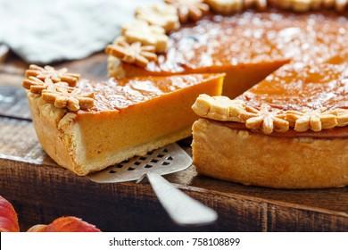 Piece of homemade pumpkin pie on a metal spatula closeup, selective focus.