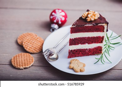 Piece of a homemade red velvet cake on a plate with cookies and Christmas decoration around