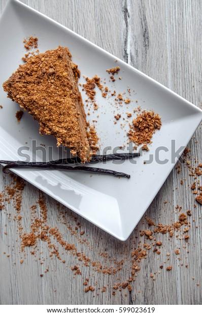 piece of honey cake with vanilla sticks