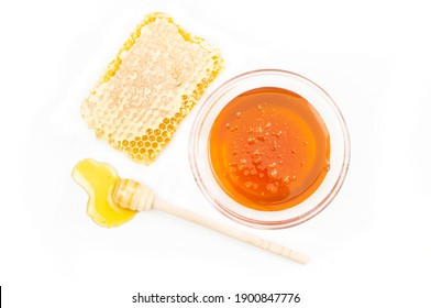 Piece of honeycomb, organic fresh liquid honey with dipper isolated on white background, healthy food
