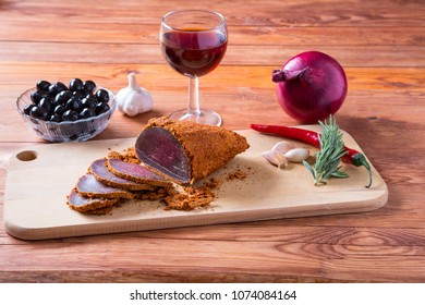 A piece of jerky beef Pastirma, olives, onion, garlic and a glass of red wine on a timbered table