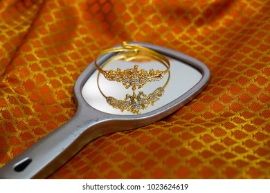 A piece of jwellery on a hand mirror