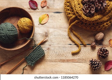 A piece of knitting with wooden needles and yarn among leaves and pine cones, autumn knitting.