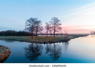 Piece of land in a semi-frozen ditch with bare tree silhouettes in winter morning during sunrise.
