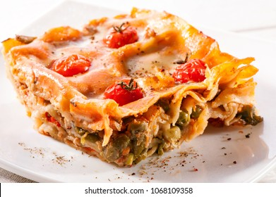 piece of lasagna close-up decorated with cherry tomatoes on white plate