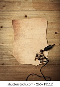 Piece of leather and tattoo machine on vintage wood desk
