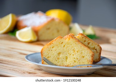 Piece of lemon cake on plate on rustic wooden board with full pie and lemons on background. Easy recipe of citrus dessert for everyday cooking. Homemade bakery by classic recipe.
