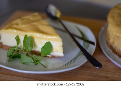 a piece of lemon cheese cake with pepermint on the plate with long tea spoon on wood bamboo desk