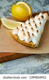 A piece of lemon tart decorated with a slice of lemon on a wooden board. Gray textured background. Beautiful serving dishes. Dessert. Food chain