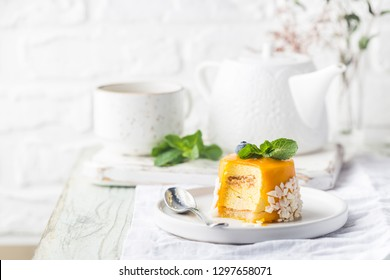 Piece of mango mousse cake on plate over white wooden table.