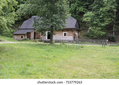 A piece of meadow and a wooden building in the background with forest in the background.