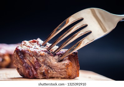 piece of meat on a fork, dark background