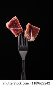 Piece of meat on a fork isolated on black backgroud. Fresh steak with fork