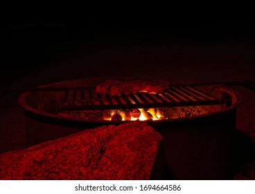 A piece of meat on a round fire bowl with grill