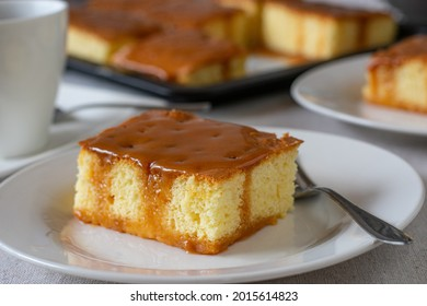 A piece of Milk cake with caramel topping on a plate with fork