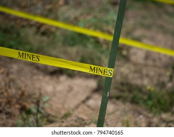 "Piece of the mine field with green props and yellow tape with the word ""Mines"" on it"