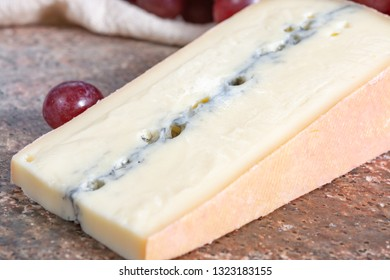 Piece of Morbier semi-soft cow milk French cheese with black mold layer