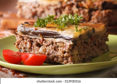 Piece of moussaka with fresh tomatoes on a green plate macro. horizontal