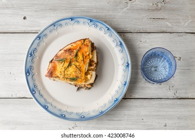 Piece of moussaka on the ceramic plate on the white table top view