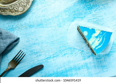 piece of mousse cake with blue glaze on the white-blue wooden background. Looking like silver, vintage metal dish, fork, knife and blue cloth napkin on the table. Horizontal Top view with copyspace