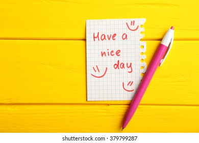 Piece of note paper on yellow wooden background