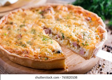A piece of onion cheese quiche or pie sprinkled with parsley on wooden table. Horizontal