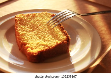 Piece of orange cake, on a white plate with fork