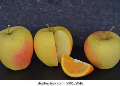 A piece of orange fits perfectly into an apple