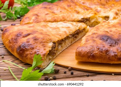 piece of Ossetian meat pie on a wooden background
