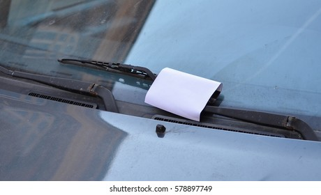 a piece of paper between the windscreen and wiper of a car