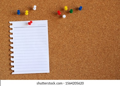 Piece paper of blank white note pad stick colorful push pin red to a cork board. empty space for text write a note.