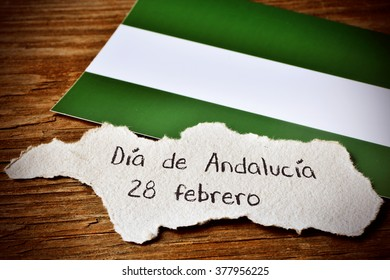a piece of paper in the shape of Andalusia, in Spain, with the text Dia de Andalucia 28 de febrero, Day of Andalusia February 28, written in Spanish, and its regional flag