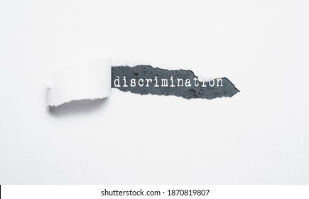 A piece of paper torn off revealing the discrimination inscription. Concept of racial equality, equality, non-discrimination.