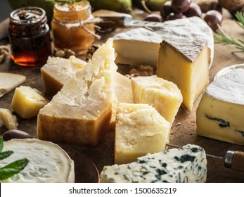 Piece of Parmesan cheese and assortment of different cheeses at the background.