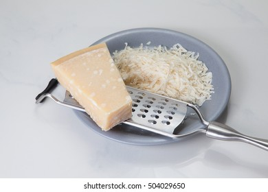 Piece of Parmesan cheese with metal grater and grated parmesan on a grey plate.