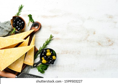 Piece of Parmesan cheese on a white wooden background. Traditional Italian cheese. Top view. Free space for your text.