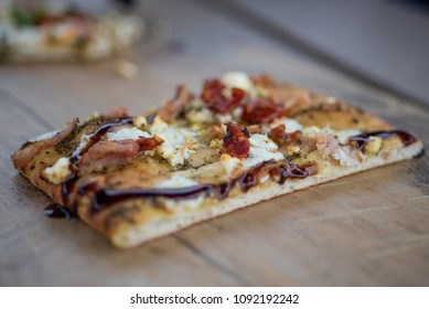 Piece of Pasture Pesto Flatbread with Smoked Chicken, Sun-dried Tomatoes, Fresh Mozzarella and  Arugula