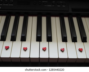 A piece of piano, white and black keys with small red hearts