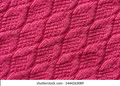 Piece of pink knitted fabric, background or texture. Knitting yarn handmade.
