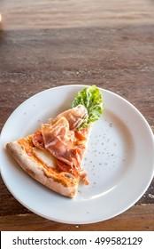 piece of pizza parma ham and rocket salad