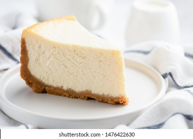 Piece of plain New York Cheesecake on white plate, closeup view. Tasty creamy dessert cake or ice cream cake