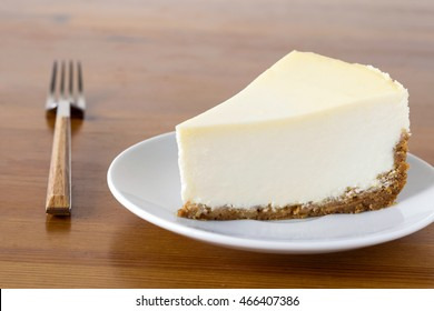 Piece of plain New York Cheesecake on white plate on wooden table, close up view