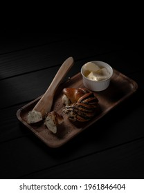 Piece of poppyseed bread roll, butter and wooden knife on wooden tray